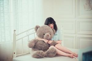 момиче на легло, което е прегърнало играчка
